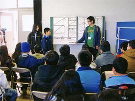 健診の流れと、健診項目を外国人学校の子どもたちに説明する教育学部の先生